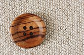 Vintage wooden button on handwoven cotton fabric.  Natural side lighting to emphasize texture.  Conc
