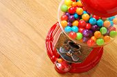Colorful bubble gum in gumball machine with wood grain background.  Close-up with shallow dof.  Copy space included.