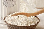 Flour still life with bowl of unbleached flour and old-fashioned canister on marble table.  Close-up with shallow dof.