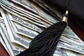 Higher education conceptual image with graduation cap and tassel on american currency.  Macro with e