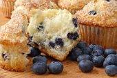 Freshly baked blueberry muffin split in half with additional muffins in the background and extra berries.  Macro with shallow dof.