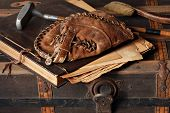 Vintage still life with antique baseball glove, golf club and scrapbook on rustic old steamer trunk.