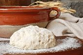 Freshly prepared bread dough with rustic bowl, homespun fabric and wheat spikes against stone backgr