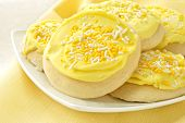 Freshly baked sugar cookies with lemon frosting and sprinkles.  Macro with shallow dof.