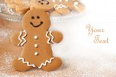 Smiling gingerbread man with additional cookies and dusting of confectioners sugar in background.  M