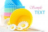 Colorful silicone baking cups with daisies made of cake icing on white background with copy space.