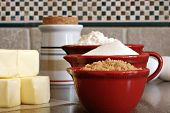 Ceramic measuring cups filled with flour and sugar along with eggs and butter on kitchen counter.  M
