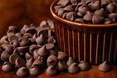 Chocolate chips overflowing from brown ceramic ramekin onto wood table.  Macro with shallow dof.