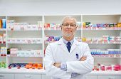 medicine, pharmacy, people, health care and pharmacology concept - smiling senior male pharmacist in poster