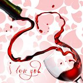Heart from pouring red wine in goblet isolated on white