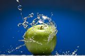 Green apple with water splash on blue background