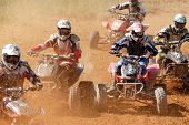 foto of dirt-bike  - Group of quad racers making the first turn of race - JPG