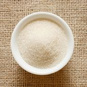 Cane sugar in a bowl on a background