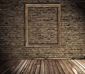 old grunge interior with blank picture frame against wall