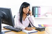 Serious Black Businesswoman On Phone At Desk