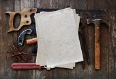 tools against wooden wall with stack of old paper