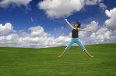 Beautiful happy woman jumping on a green field