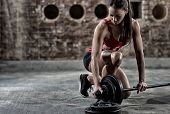 sexy young fitness woman preparing to lift some heavy weights poster
