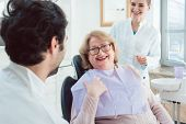 Dentist and assistant greeting senior patient in their surgery  poster