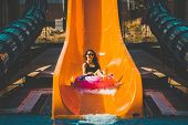 Pretty Lady In Black Bikini Going Down On The Inflatable Ring By The Slide In The Aqua Park. Summer  poster