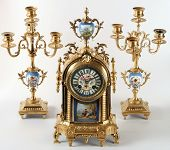 An antique clock with floral decor and painted enamel. Two sconces are in the suit.