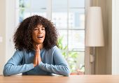 African american woman at home begging and praying with hands together with hope expression on face  poster