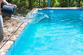 Man Pours Of Disinfectant From Bucket In Outdoor Swimming Pool On Backyard Of Country House poster