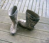 picture of mukluk  - Two muddy rubber work boots on a wooden porch - JPG