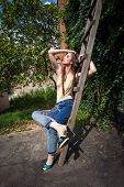 young woman in backyard summer fashion blue embroidered jeans and bodysuit-nude color and high heel  poster