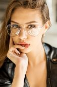 Lifestyle photo of young cheerful woman in fashion transparent glasses wearing a rock black style le poster