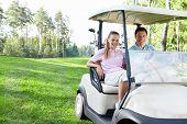 Jovem casal no carro de golfe