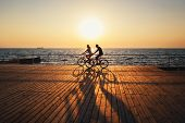 Couple Of Young Hipsters Cycling Together At The Beach At Sunrise Sky At Wooden Deck Summer Time. poster