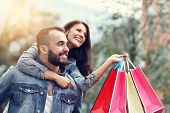 Portrait of happy couple with shopping bags after shopping in city poster