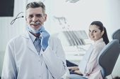 Doctor And Mask After Treatment. Concept Of Patient. Portrait Of Smiling Dentist. Smiling Girl On Ba poster