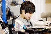 Disabled Four Year Old Boy Studying Or Reading In Wheelchair