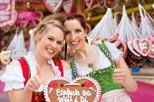Young women in traditional Bavarian clothes - dirndl or tracht -with a gingerbread souvenir heart on