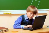 Serious schoolboy studying with his laptop at classroom.
