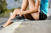 runner with ankle injury holds foot to reduce pain. running problem for athlete training outdoors
