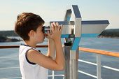 Boy stands on board of ship and looks through binoculars at beautiful landscape
