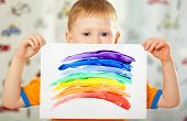 boy with painted  rainbow on paper