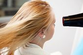 Blond hair of a young woman being dried by blow dryer at parlor