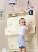 little child baby boy standing in bed indoors in baby room