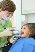 Jovem dentista mantém a aspiração de saliva e afiar broca, menina feliz abre a boca em clínica odontológica.