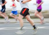 picture of competing  - group of runners compete in the race blurred motion