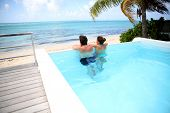 Couple looking at the sea from swimming-pool