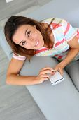 Upper view of woman in sofa using smartphone