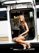 Sexy girl sitting in limousine door, smiling, wearing mini dress and high heels.