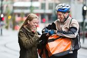 Courier delivery man with backpack showing digital tablet to young woman on street