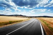 stock photo of fall-wheat  - asphalt road in Tuscany Italy - JPG