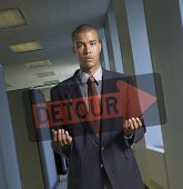 Portrait of businessman holding transparent detour sign